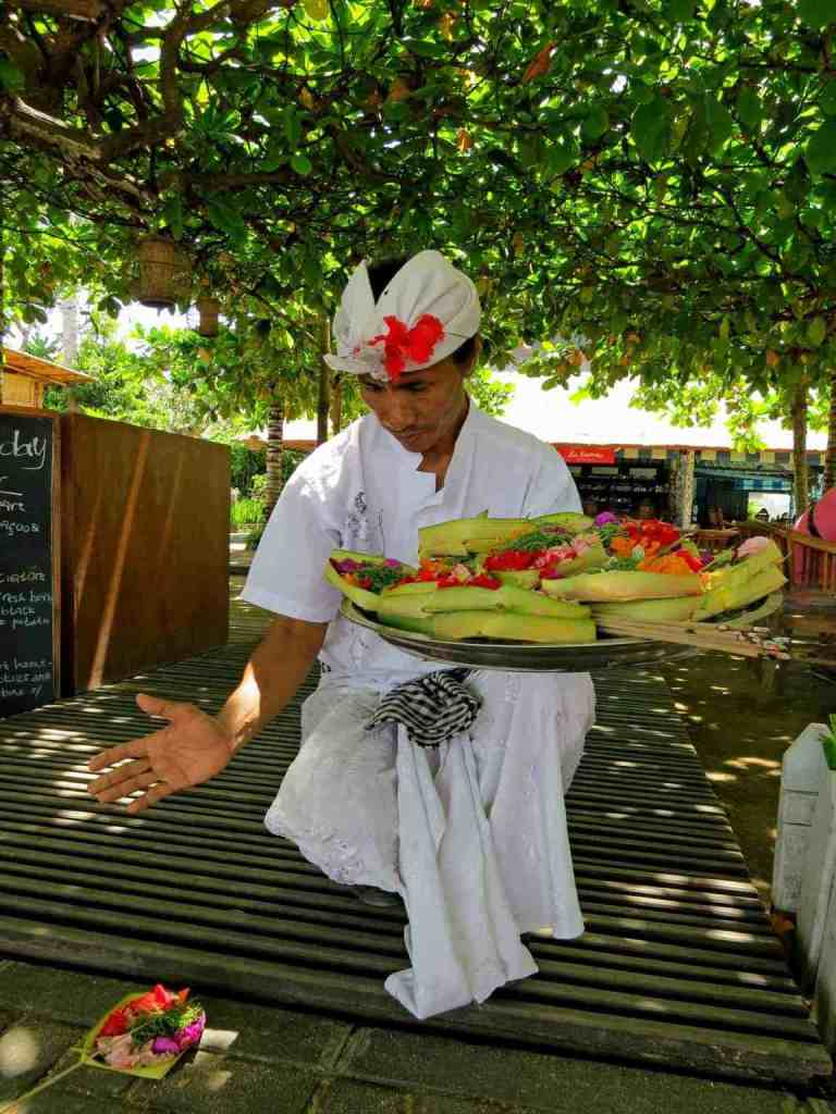 Balinese man laying out an offering
